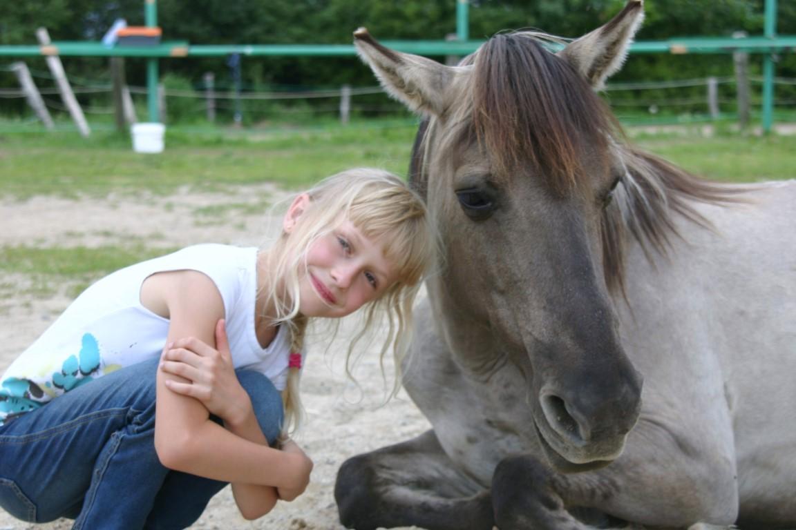 Dziewczynka tuląca się do konia